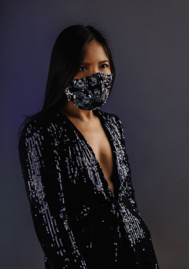 A woman wearing a sequin top and facemask